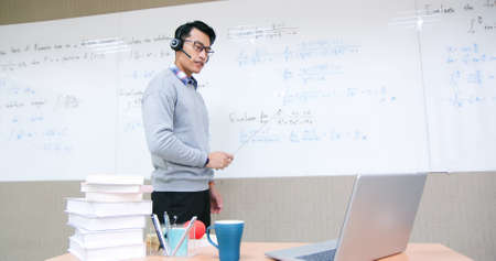 asian male professor wearing headsets teach calculus online through laptop in classroom Banco de Imagens