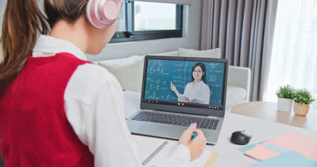 rear view of asian girl is learning math online through listening to female high school teacher teaching trigonometric function by laptop at home