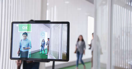 AI Facial Recognition Camera scanner identifying person in a crowd of asian business people