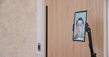 facial recognition concept-Asian man using face scanner to unlock door in office building Banco de Imagens