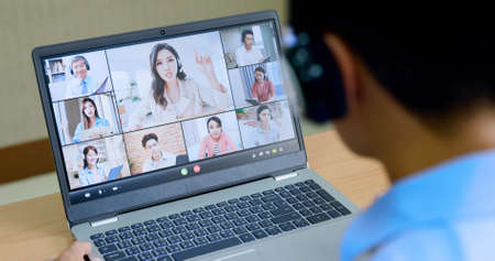 telework concept-Asian man use laptop and headset to join a video meeting at home Banco de Imagens