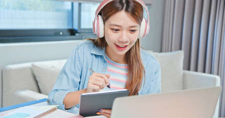 close up of asian college female student is learning and looking online course through laptop with writing notes on digital tablet at home Banco de Imagens