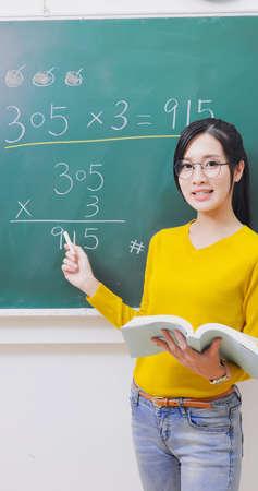 asian elementary school female teacher teach math online through mobile phone in classroom Banco de Imagens