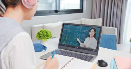 rear view of asian girl is learning math online through listening to female high school teacher teaching trigonometric function by laptop at home and write down the note Banco de Imagens
