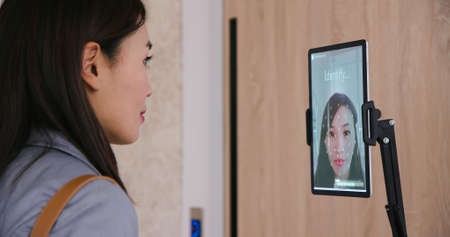 facial recognition concept-Asian businesswoman using face scanner to clock in work and unlock office door