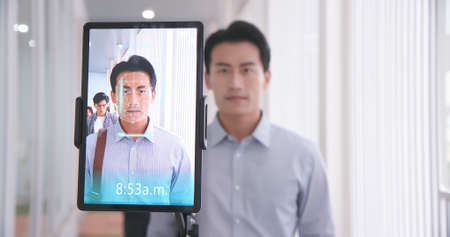 facial recognition concept-Asian businessman using face scanner to clock in work and check body temperature Banco de Imagens