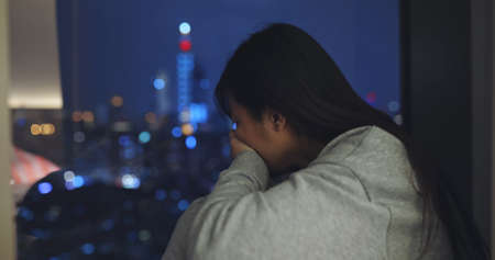 asian woman feel depressed and crying near window at home Banco de Imagens