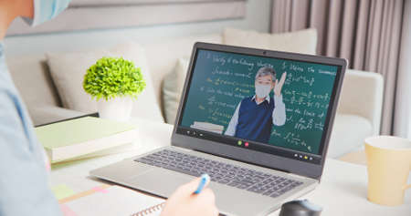 side view of asian girl wearing face mask is learning math online through listening to senior male college teacher teaching calculus by laptop at home and write down the note Banco de Imagens