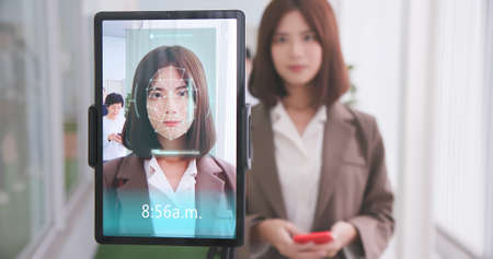 facial recognition concept-Asian businesswoman using face scanner to clock in work and check body temperature