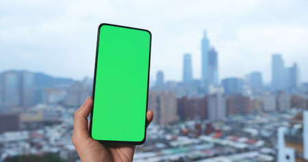 woman holds green screen smartphone in city