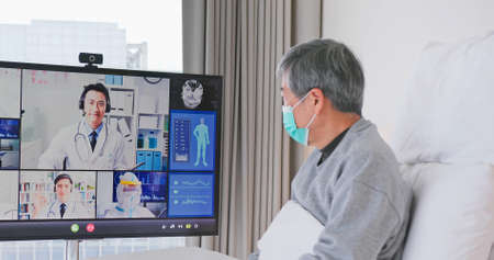 Telemedicine concept-asian senior man patient lying on bed has video call with doctor team by big screen TV in a hospital ward or at home