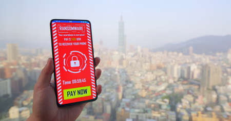 woman read ransomware message on her mobile phone in city Banco de Imagens