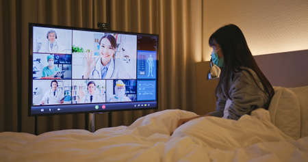 Telemedicine concept-asian woman patient lying on bed has video call with doctors team by big screen TV in a hospital ward or at home Banco de Imagens