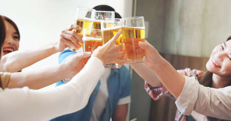 slow motion of group of asian happy friends toasting beer in restaurant
