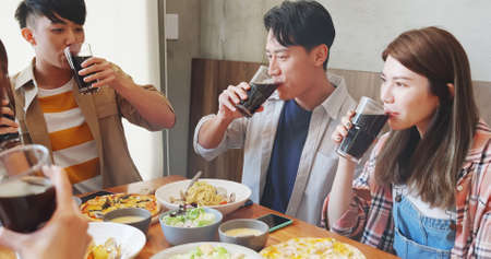 Group of asian happy friends drinking juice or wine in restaurant