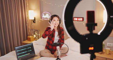 asian woman with microphone has live stream and singing through smartphone in bedroom at home