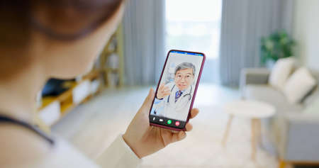 Telemedicine concept-coughing asian female has video chat with male doctor by smartphone