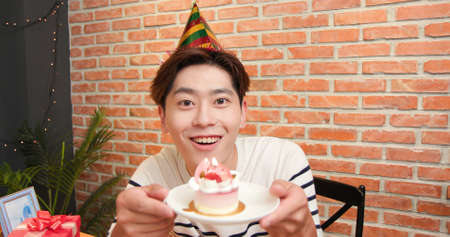 asian young man has video chat online is saying happy birthday and giving cake for his girlfriend-look at you