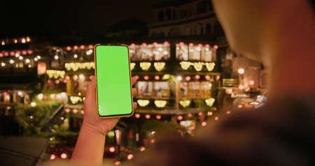 rear view of Asian female tourist is using green screen smatphone while traveling at Jiufen old village in the evening Banco de Imagens