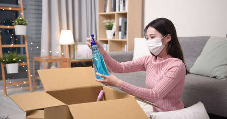 asian young woman wearing surgical face mask is opening online shopping parcel cardboard box with sanitizing products during the epidemic prevention period