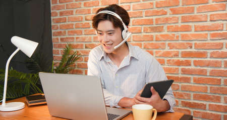 telework concept-Asian businessman wearing headset is joining video meeting by laptop computer and using digital tablet at home