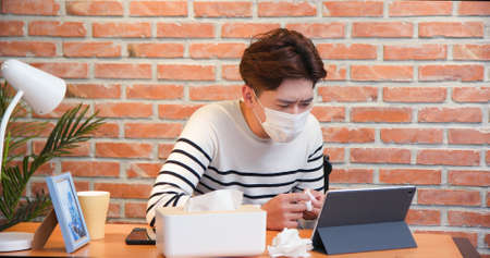 Telemedicine concept-asian young male patient wearing facial mask and talking to the doctor online by digital tablet