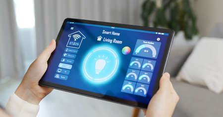 asian woman use smart home app to turn on the light with tablet pc