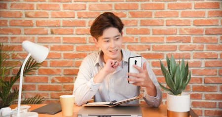 asian young businessman uses smartphone to join a video meeting and writes notes at home Banco de Imagens