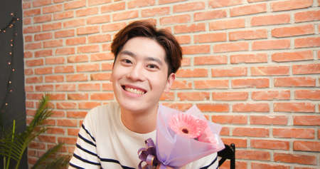 asian young man is having video chat online to celebrate happy valentine day and giving flowers for his girlfriend
