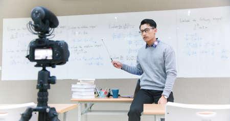 asian male professor teach calculus online through camera in classroom