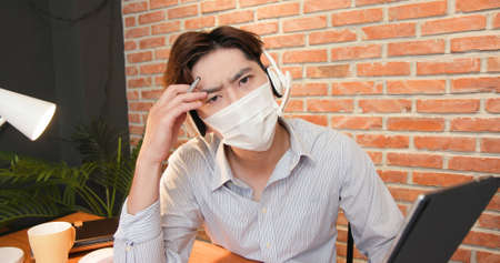 telework concept-Asian man wearing face mask and headset is very upset to get some trouble about his work on a video meeting at home
