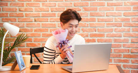 asian young man has video chat online by laptop while celebrating valentine day and giving flowers for his girlfriend