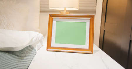 close up of photo frame with green copy space on cabinet in bedroom at home
