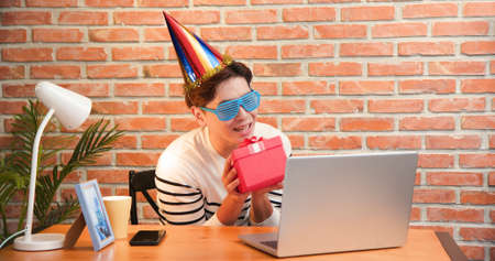 funny asian young man wearing birthday hat has video chat online by laptop while celebrating and giving present box for his friend
