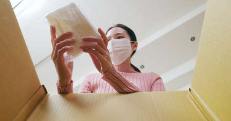 asian young woman wearing surgical face mask is opening online shopping parcel cardboard box during the epidemic prevention period Banco de Imagens