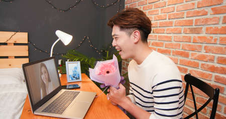 side view of asian young man has video chat online by laptop-saying happy valentine day and giving flowers for his girlfriend