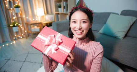 asian young woman wearing birthday hat has video chat online by laptop while celebrating and giving present box for her friend Banco de Imagens