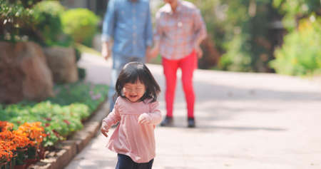 Authentic shot of asian little girl is running happily-senior grandparent are behind her