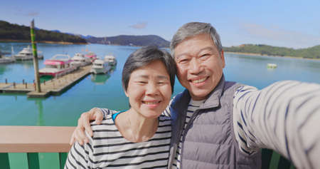 Asian elderly couple have video chat by mobile phone happily outdoor near harbor