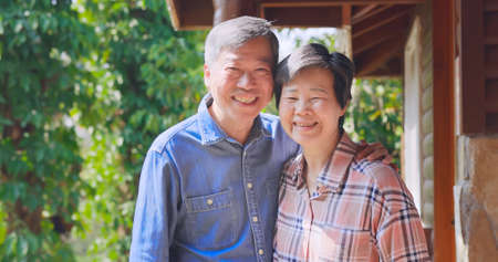 Authentic shot of Asian senior retired man enjoy travel with his wife and they smiling at you