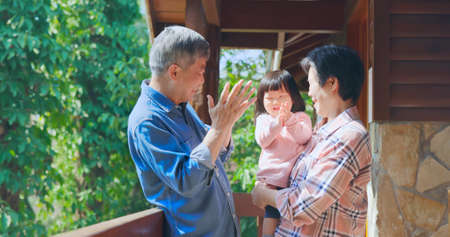 Authentic close up of Asian senior retired grandparent have fun with their granddaughter while they are traveling
