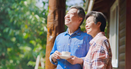 Authentic shot of Asian senior retired man drinking coffee is enjoying travel with his wife and they looking outside