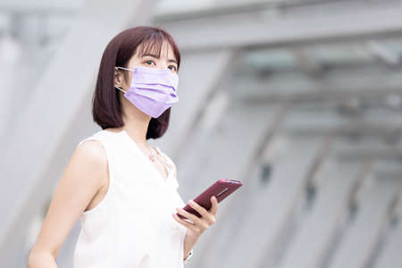 asian young businesswoman wear face mask and use smart phone with suitcase on her business trip while waiting for picking up