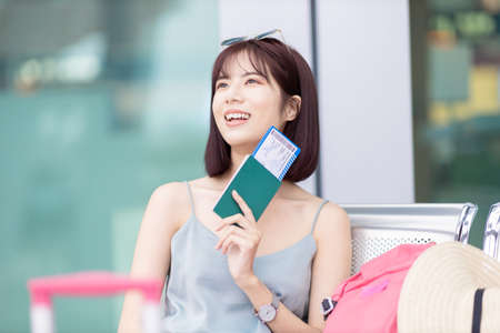 smiling Asian female traveler ready to take her flight for summer vacation at the airport Banco de Imagens