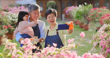 Authentic shot of asian retired grandparent have video chat on smart phone with their granddaughter in the garden
