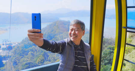 asian senior man take selfie inside the cable car cabin while traveling Banco de Imagens