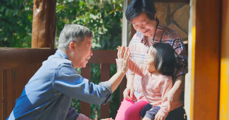 Authentic close up of asian senior retired grandparent have fun with their granddaughter while traveling