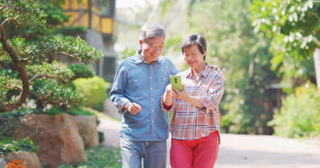 Authentic shot of asian senior couple are wandering on walkway and sharing social media content by mobile phone Banco de Imagens