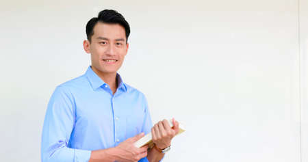 asian young male teacher holds a book and smiles at you in classroom Standard-Bild