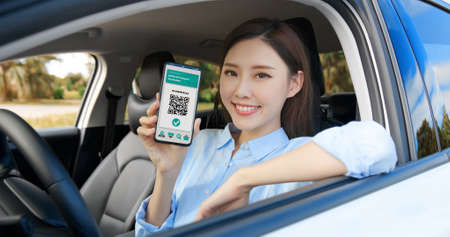asian female driver shows health passport on mobile phone which indicates a vaccination against covid-19 in car Stock fotó